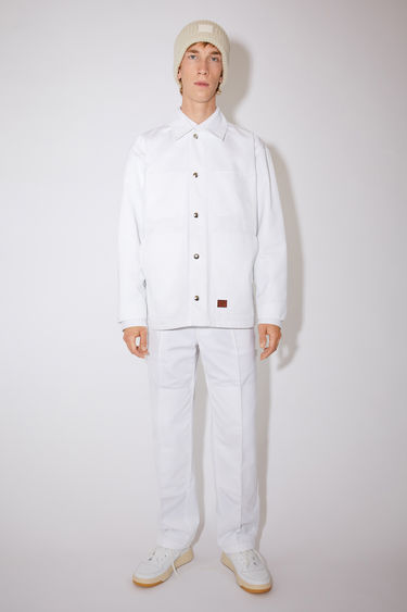 Acne Studios white unlined workwear jacket is made of crisp cotton twill with a face logo patch.