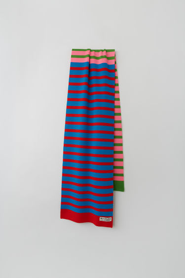 Acne Studios launches an exclusive range with Swedish artist Jacob Dahlgren. As part of the collaboration, the blue multi scarf is finely knitted from wool and patterned with horizontal stripes.