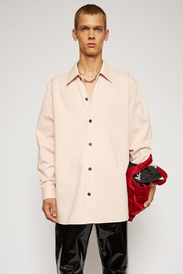 Acne Studios old pink shirt is made from cotton twill that's been garment dyed for softness. it's crafted to a boxy silhouette that falls loosely across the frame with a point collar and button-down front.