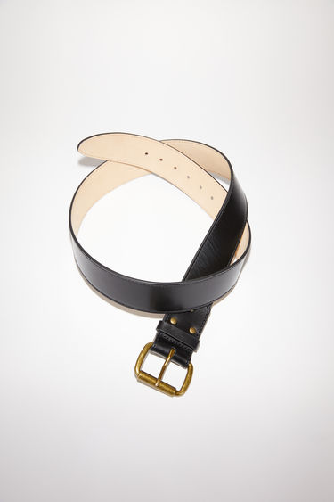 Acne Studios black belt is crafted to a wide dimension from high-shine leather and features an antiqued gold-tone buckle.