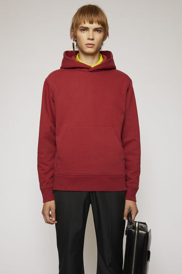 Acne Studios burgundy hooded sweatshirt is made from heavyweight brushed jersey and completed with a kangaroo pocket and a ribbed hem.