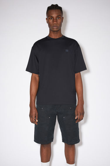 Acne Studios black relaxed fit t-shirt is made of organic cotton with a ribbed crew neck and face logo patch.