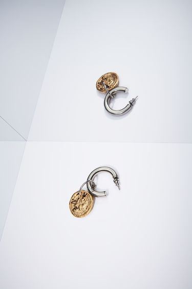Acne Studios antique silver/antique gold pierced earring features a branded coin and is sold as a single earring.