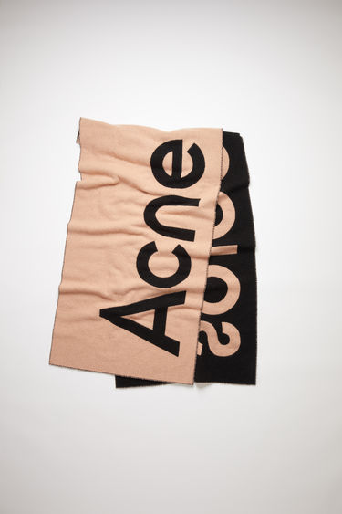 Acne Studios pink/black oversized scarf is made of a soft wool blend featuring bold, contrasting logo lettering on both sides.