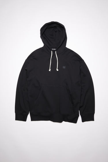 Acne Studios black oversized hooded sweatshirt is made of organic cotton with a face patch and ribbed details.