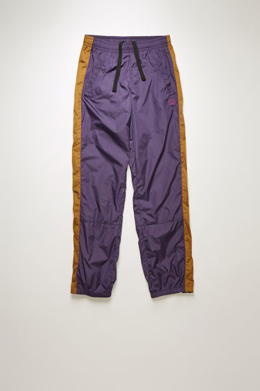Acne Studios aubergine purple track pants are made from shell and has an elasticated waistband and hem. They are accented with a face-embroidered patch and stripes down the sides.