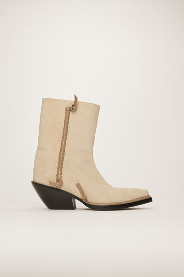 Acne Studios beige boots offer a contemporary take on the traditional cowboy boots. Crafted from suede, they rest on a slanted stacked heel and are accented with leather knots and whipstitched seams.