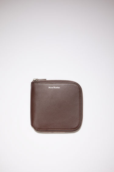 Acne Studios dark brown medium-sized leather wallet has compartments for cards, coins, and documents.