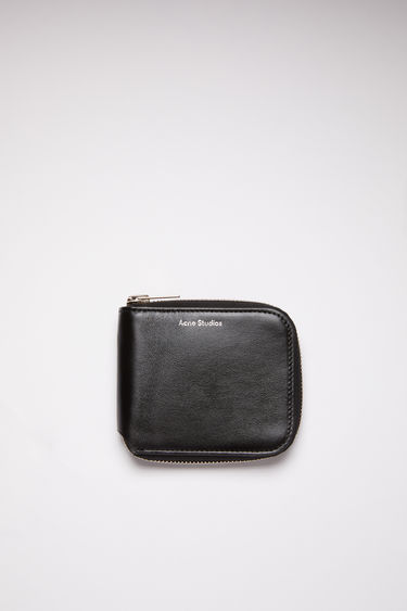 Acne Studios black compact zip wallet is made of smooth leather with two card slots, a bill sleeve, and a zipper closure.