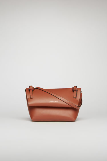 Acne Studios almond brown mini purse is crafted from soft cow leather and detailed with an obi-inspired knot on each end of the crossbody strap.