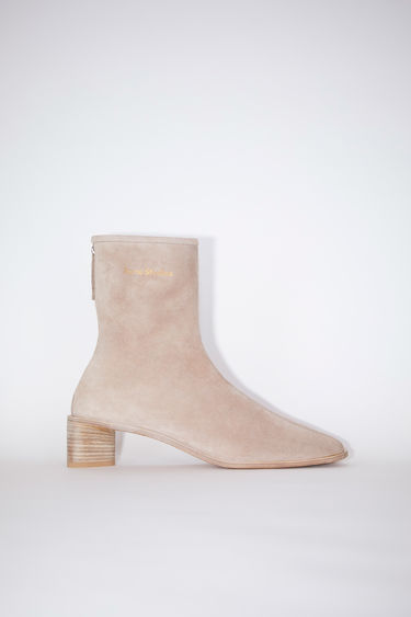 Acne Studios beige/ecru square toe booties are made of suede with Acne Studios branding.