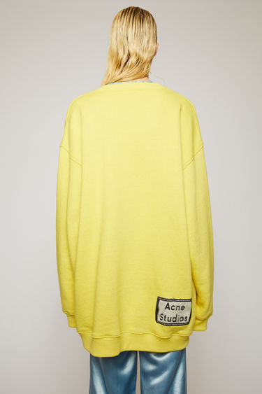 Acne Studios canary yellow sweatshirt is crafted for an oversized fit from midweight loopback jersey and adorned with a label patch that's left with loose thread for a subtle note of texture.