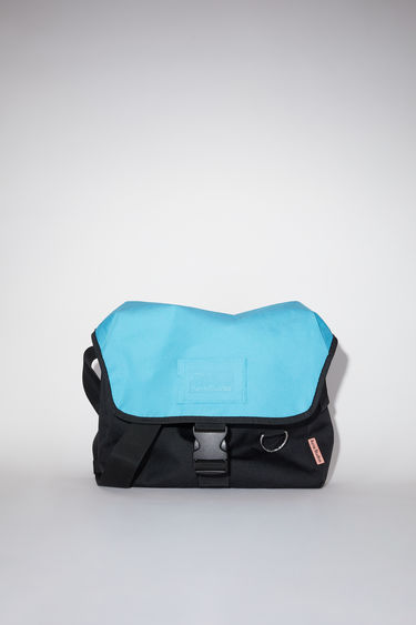 Acne Studios black/blue large, durable messenger bag has a clear vinyl ID pocket, strap with decorative stitching, and an Acne Studios logo tab.