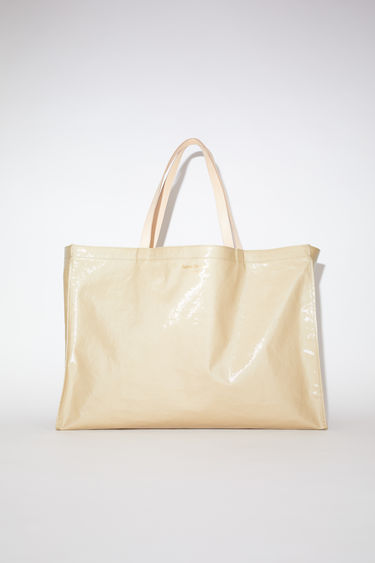 Acne Studios beige oilcloth tote bag features Acne Studios branding and leather handles and inside pocket.