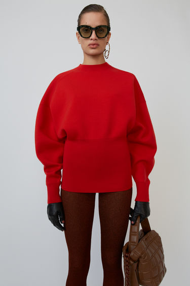 Acne Studios bright red sweater is shaped with dolman sleeves and a wide, ribbed waist.