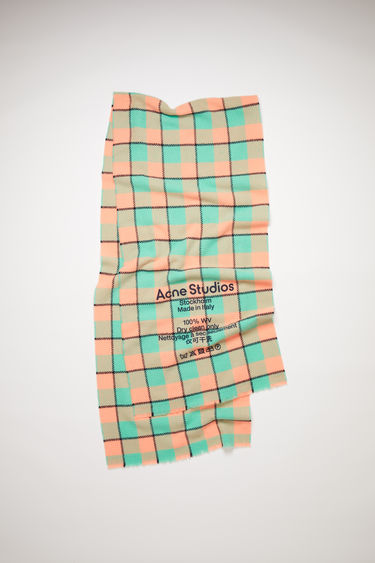 Acne Studios salmon pink/mint green narrow, checked scarf is made of wool with a large, printed care label.