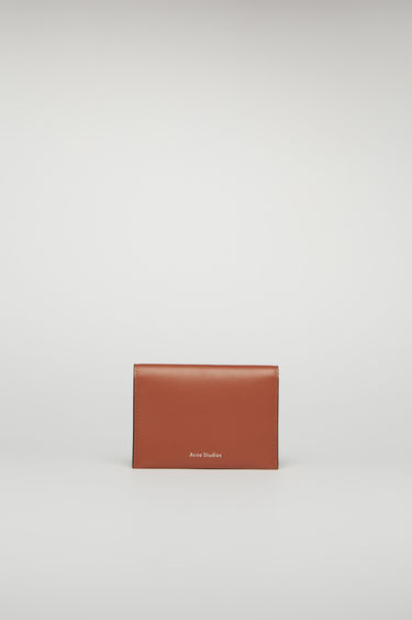 Acne Studios almond brown bifold cardholder is crafted from smooth leather and features four card slots and a silver stamped logo on the front.