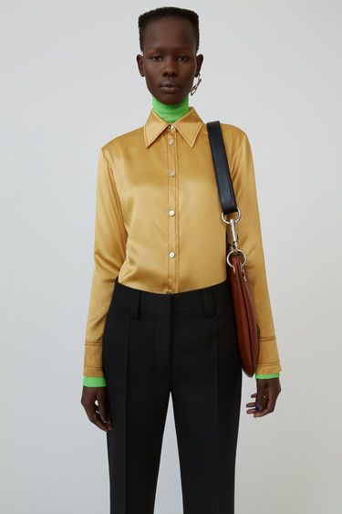 Acne Studios yellow gold shirt is crafted from lightweight satin and accented with topstitches and mirrored buttons.