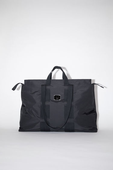 Acne Studios black tote bag is made from technical ripstop, featuring two different cotton canvas handles woven in the body of the bag. It has a zipper closure and a spacious interior with a mesh pocket and key ring.