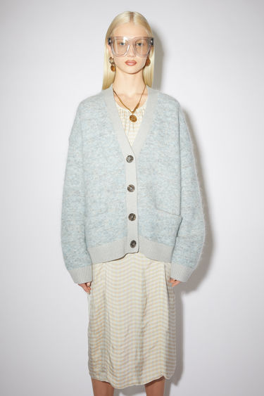Acne Studios light grey/blue cardigan is knitted from a soft mohair and wool-blend to an oversized silhouette with dropped sleeves and features two front patch pockets and ribbed placket, cuffs and hem.