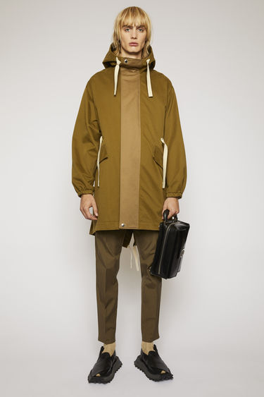 Acne Studios olive green/taupe grey parka is cut from technical cotton twill with a tonal placket and features a drawstring hood, waist and hem to adjust the fit.