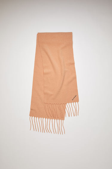 Acne Studios dusty pink scarf is crafted from soft boiled wool-blend and finished with fringed trims and an embroidered logo.