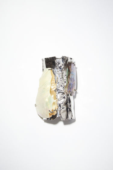 Acne Studios silver/cream white cuff bracelet is made of brass, featuring a broken shell.