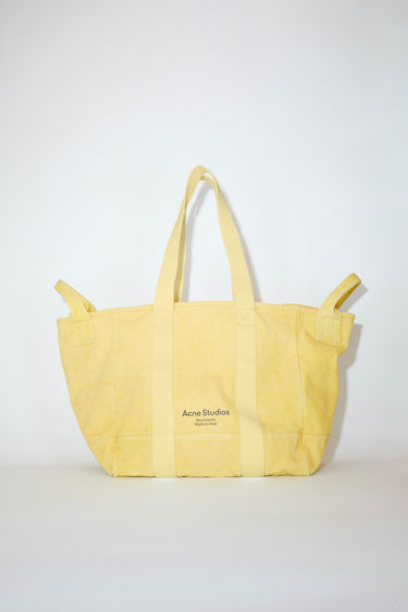 Acne Studios yellow canvas tote bag is made of cotton with webbing shoulder straps and carrying handles.