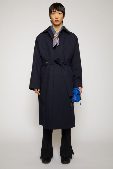 Acne Studios navy trench coat is crafted from cotton twill to an oversized silhouette features two front welt pockets, a concealed button placket, and a matching tie belt.