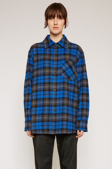 Acne Studios ink blue checked shirt is made from cotton flannel and features front patch pockets - forward with one and in reverse with the other - then accented with a face-embroidered patch.
