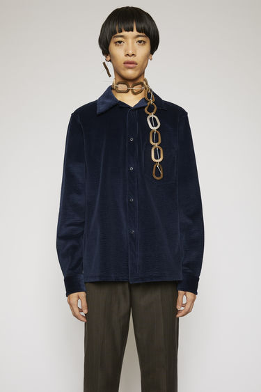 Acne Studios navy shirt is crafted from soft corduroy to a boxy silhouette with a chest pocket and snap button closures.