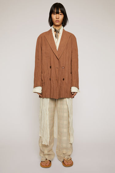Acne Studios mink brown double-breasted jacket is crafted from creased linen with peak lapels and three patch pockets and features an embroidered care instruction label at back neck.