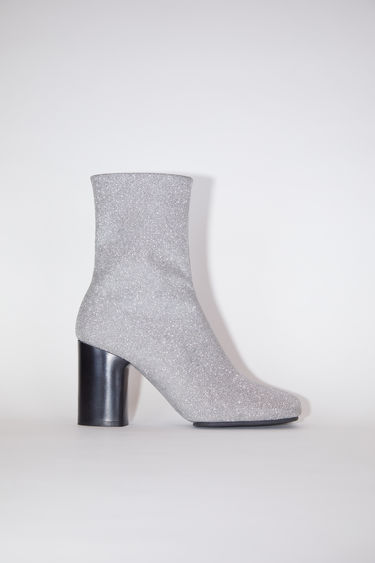 Acne Studios silver glitter boots have square toes and chunky heels.