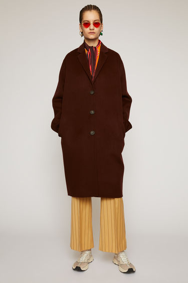 Acne Studios maroon red coat is crafted from double-faced wool to a relaxed silhouette with notch lapels, then fastens with buttons through the front.