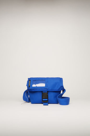 Acne Studios deep blue messenger bag is crafted to a boxy shape with raw-edged trim and features an adjustable shoulder strap and a transparent card pocket on the flap.