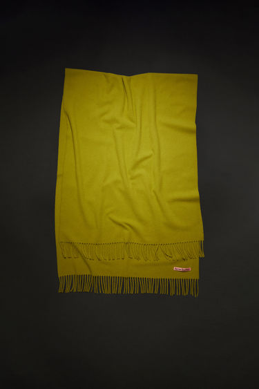 Acne Studios olive green oversized fringed scarf is made of pure wool, featuring a label in one corner.