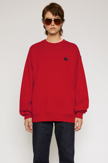 Acne Studios cherry red/black sweatshirt is crafted from midweight loopback fleece to a loose silhouette and finished with a face-embroidered patch on the chest.