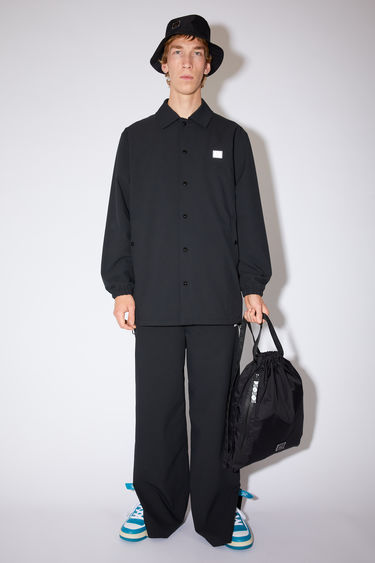 Acne Studios black coach jacket is made of a structured polyethylene twill with a face logo patch at the chest and a large face print on the back.