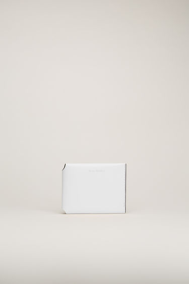 Acne Studios white/black trifold card wallet is crafted from soft grained leather with a coin pocket, note sleeve and four card slots and features a silver stamped logo on front.