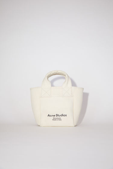 Acne Studios beige small shopper bag is made of thick cotton canvas with Acne Studios branding on the front.
