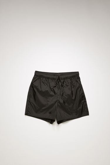 Acne Studios black swim shorts are crafted from technical nylon with front and back pockets and finished with an elasticated waistband with round drawstrings.