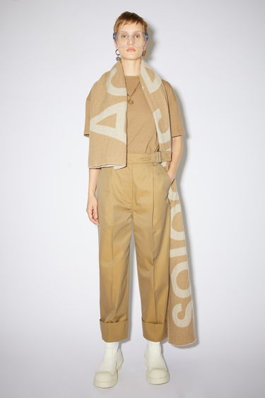 Acne Studios hazel beige casual trousers are made of cotton with a high-waisted, wide leg fit and belt detail.