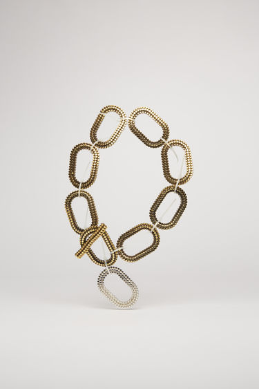 Acne Studios antique gold chain necklace is crafted from gold and silver tone brass and sculpted with a circle pattern and secured with cable zip ties.