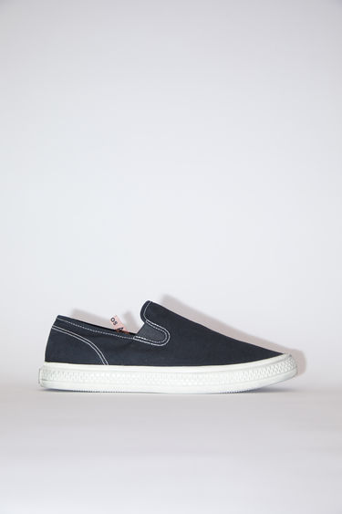 Acne Studios black/off white distressed canvas slip-on sneakers have rubber soles.