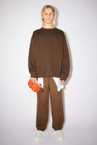 Acne Studios chestnut brown oversized crew neck sweatshirt is made of organic cotton with a face patch and ribbed details.