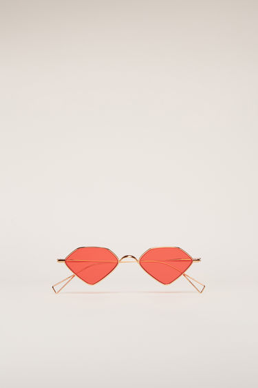 Acne Studios rose gold/red sunglasses are crafted from rose gold-tone metal frame with a pentagonal shape. They are set with tinted lenses and finished with curved metal tips and adjustable nose pads.