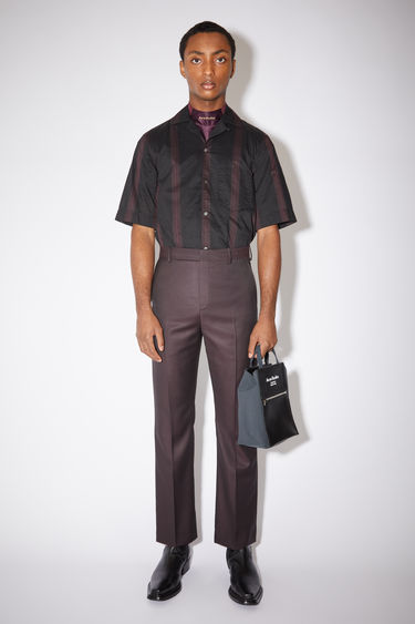 Acne Studios aubergine purple tailored trousers are made of a wool blend with a slight flare.