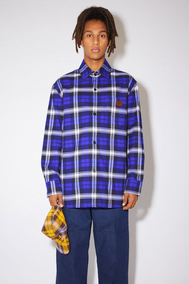 Acne Studios electric blue/off white checked flannel overshirt is made of cotton with a chest pocket featuring a leather face patch.