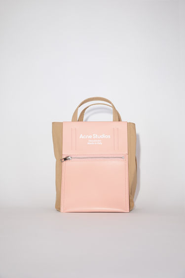 Acne Studios Baker Out brown/pink bag is made from durable nylon with a papery texture and crafted in a boxy shape. It features a leather zipped pocket with a white printed logo on the front.