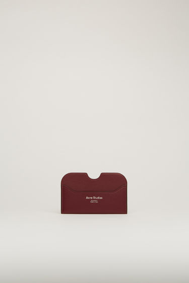 Acne Studios Elmas S burgundy cardholder is crafted from soft grained leather with three card slots and accented with a cut-out at the midpoint of the central slot.